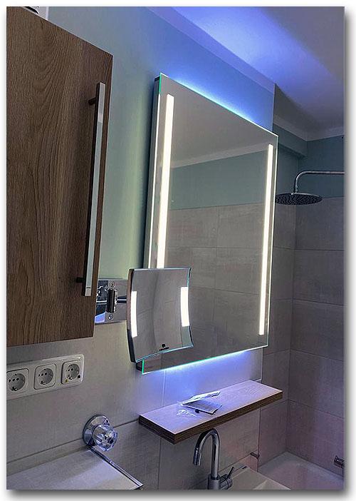 Beleuchtungsspiegel im Bad mit vertikaler Spiegelbeleuchtung rechts und links und zusätzlicher Raumbeleuchtung nach oben und unten. Die Beleuchtung des Spiegel erfolgt mit LED und ist dimmbar.